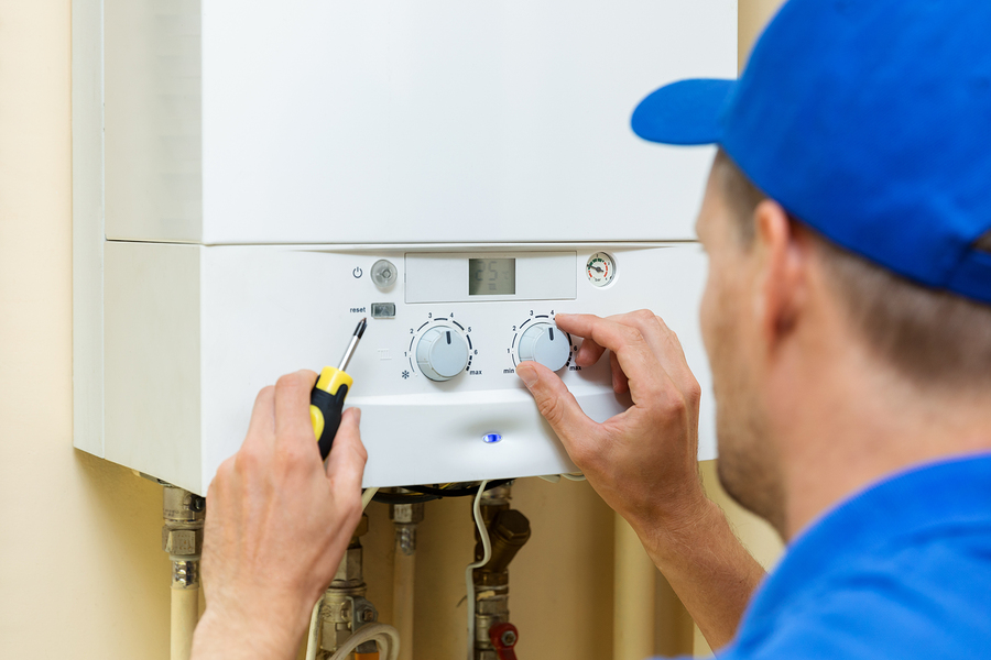 Worker setting up a hot water cylinder at home